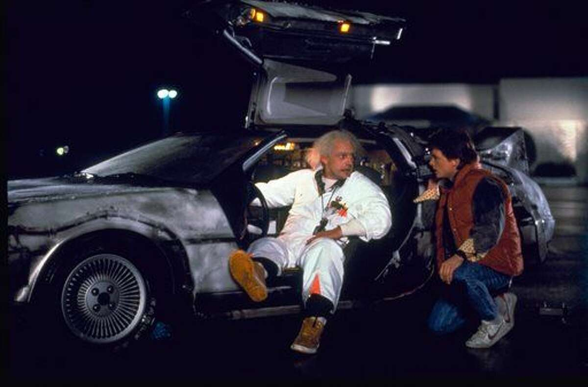 """This photo provided by Universal Pictures Home Entertainment shows Christopher Lloyd, left, as Dr. Emmett Brown, and Michael J. Fox as Marty McFly in the 1985 film, """"Back to the Future."""" Wednesday's so-called """"Back to the Future"""" Day marks the date - Oct. 21, 2015 - that characters McFly, Brown and Jennifer Parker famously journeyed to the future in the film trilogy's second installment in 1989. """"The Back to the Future 30th Anniversary Trilogy"""" and """"Back to the Future: The Complete Adventures"""" release on Blu-ray and DVD on Oct. 20. (Universal Pictures Home Entertainment via AP)"""