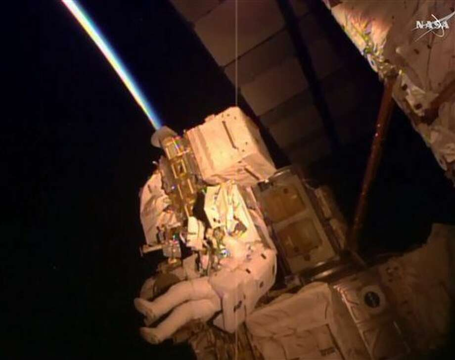 In this frame grab from NASA Television, astronaut Kjell Lindgren performs maintenance outside the International Space Station, Wednesday, Oct. 28, 2015. Lindgren and fellow astronaut Scott Kelly's to-do list included greasing the station's big robot arm, routing cables, removing insulation from an electronic switching unit and covering an antimatter and dark matter detector. (NASA via AP) Photo: HOGP