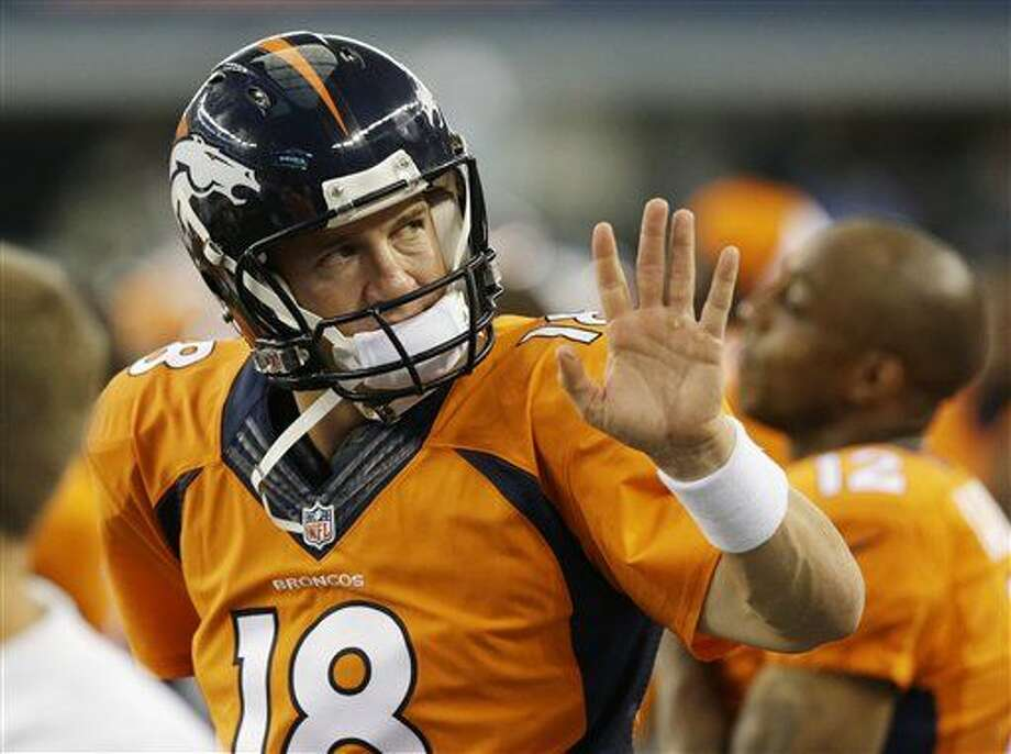 Denver Broncos quarterback Peyton Manning (18) waves to a fan in the first half of a NFL preseason football game against the Dallas Cowboys, Thursday, Aug. 28. 2014, in Arlington, Texas. (AP Photo/LM Otero) Photo: LM Otero