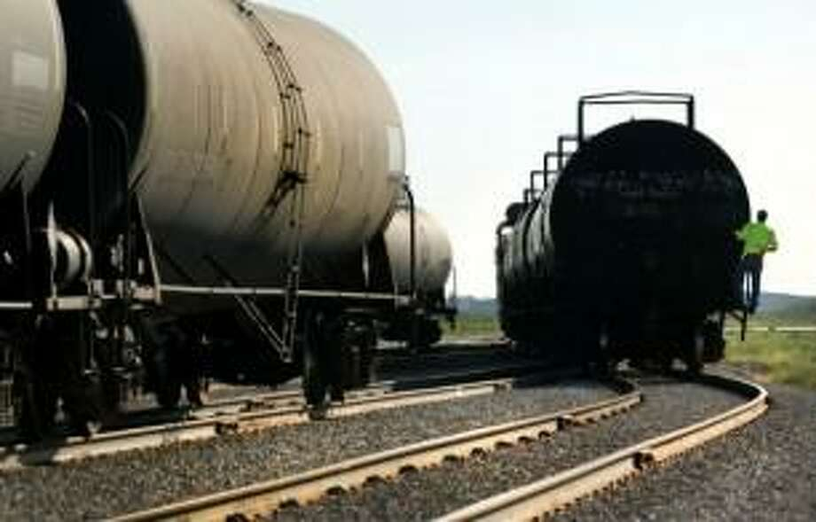A Hondo Railway worker rides on a tanker car as rail cars are moved to be unloaded. (Bob Owen/San Antonio Express-News)