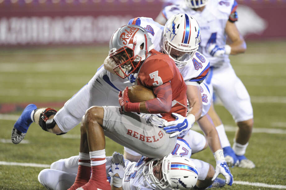 Highland runningback Deon Stewart being tackled by #46 Reid Talley and #21 Sam Gilbert