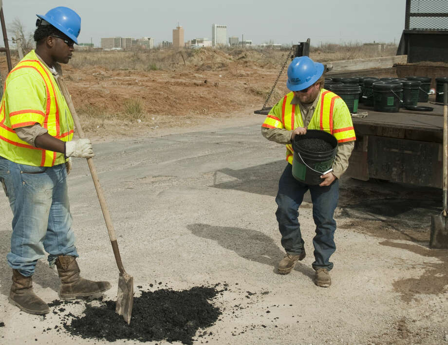 Jacoby Woods and Casey Martin, with City of Midland Transportation, use Instant Road Repair in a bucket Thursday, 1-29-15, as they demonstrate the different ways crews can fill potholes at the intersection of Cotton Flat and Francis. Tim Fischer\Reporter-Telegram Photo: Tim Fischer
