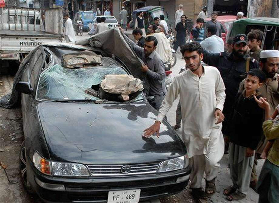 People stand near a car damaged from an earthquake in Peshawar, Pakistan, Monday, Oct. 26, 2015. A powerful 7.7-magnitude earthquake in northern Afghanistan rocked cities across South Asia. Strong tremors were felt in Kabul, New Delhi and Islamabad on Monday. In the Pakistani capital, walls swayed back and forth and people poured out of office buildings in a panic, reciting verses from the Quran. (AP Photo/Mohammad Sajjad) Photo: Mohammad Sajjad