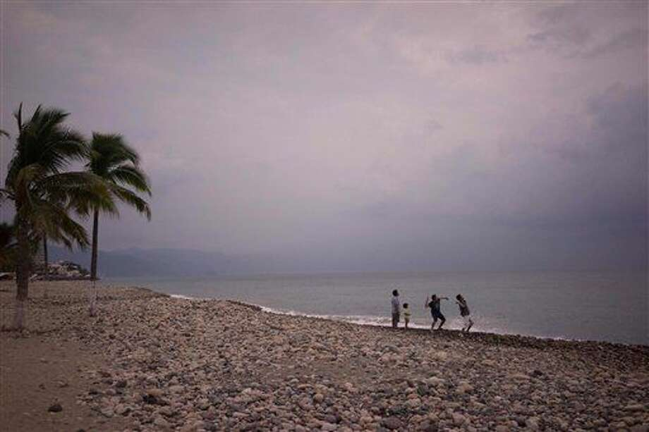 People throw stones into the ocean as hurricane Patricia nears in the Pacific resort city of Puerto Vallarta, Mexico, Thursday, Oct. 22, 2015. Hurricane Patricia grew into a monster, Category 5 storm and bore down on Mexico's central Pacific Coast, on or near Puerto Vallarta, on Thursday night for what forecasters said could be a devastating blow, as officials declared a state of emergency and handed out sandbags in preparation for flooding. (AP Photo/Cesar Rodriguez) Photo: Cesar Rodriguez