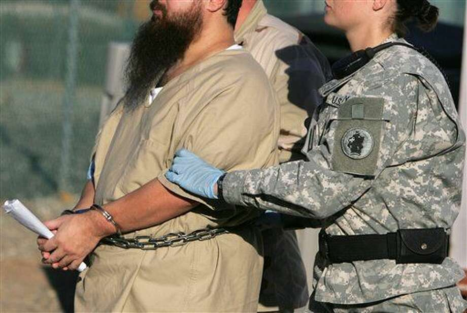 FILE - In this Dec. 6, 2006 file photo, reviewed by a U.S. Dept of Defense official, a shackled detainee is transported by a female guard, front, and male guard, behind, away from his annual Administrative Review Board hearing with U.S. officials, at Camp Delta detention center, Guantanamo Bay U.S. Naval Base, Cuba. A military judge is taking testimony on Friday, Oct. 30, 2015 about female guards at the Guantanamo Bay detention facility in Cuba. (AP Photo/Brennan Linsley, File) Photo: Brennan Linsley