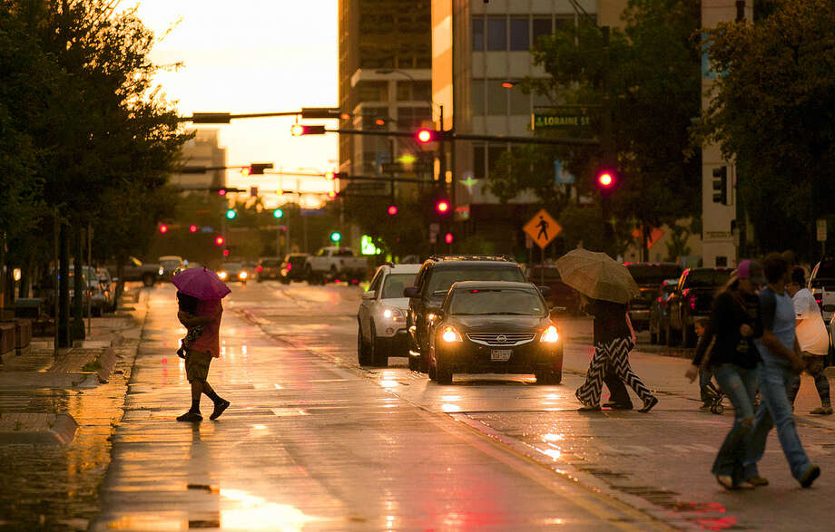 Midlanders cross Wall Street in downtown as a light rain falls Thursday, May 28, 2015.  Photo: James Durbin/Reporter-Telegram