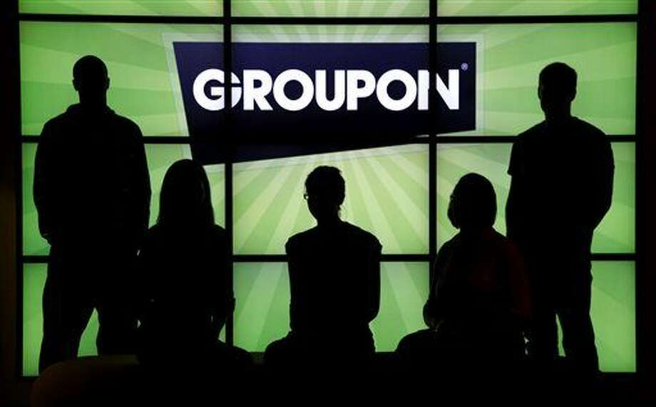 FILE - In this Sept. 22, 2011 file photo, employees at Groupon pose in silhouette with the company logo in the lobby of the online coupon company's Chicago offices. Websites like Groupon have become the go-to place for folks looking for that half-off deal on a manicure, a two-for-one offer for a fancy dinner or that all-inclusive trip that won't break the bank. But increasingly, it's also becoming the place for music fans to scoop up deep discounts on concert tickets and CDs of top-name acts. (AP Photo/Charles Rex Arbogast, File) Photo: Charles Rex Arbogast