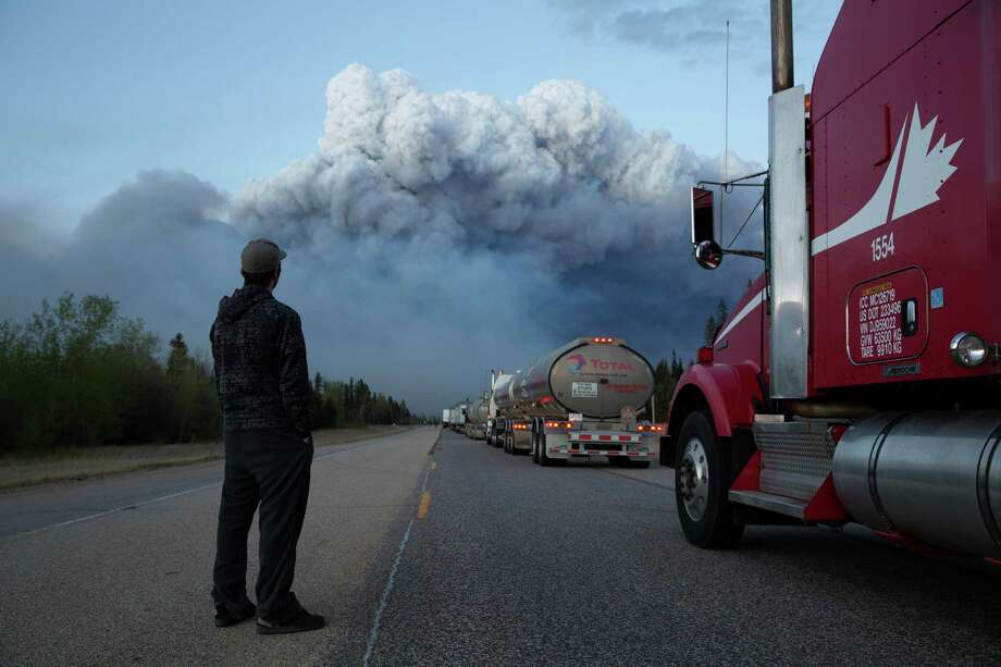 Drivers of a resupply convoy stand outside their vehicles south of Fort McMurray as a wildfire blocked the only highway to the city in northern Alberta, Canada, May 5, 2016. Nearly 25,000 of Fort McMurray's 90,000 or so residents fled north to isolated oil industry work camps when the city was ordered evacuated, but supplies there quickly ran low. (Tyler Hicks/The New York Times) Photo: TYLER HICKS, STF / NYT / NYTNS