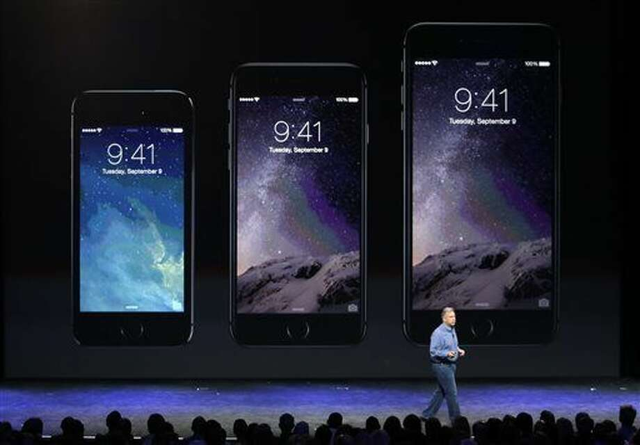 Phil Schiller, Apple's senior vice president of worldwide product marketing, discusses the new iPhone 6, center, and iPhone 6 plus, right, on Tuesday, Sept. 9, 2014, in Cupertino, Calif. (AP Photo/Marcio Jose Sanchez) Photo: Marcio Jose Sanchez