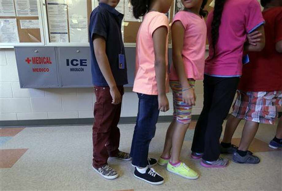 Detained immigrant children line up in the cafeteria at the Karnes County Residential Center, a temporary home for immigrant women and children detained at the border, Wednesday, Sept. 10, 2014, in Karnes City, Texas. Federal authorities want to build a similar immigration lockup facility for families in Dilley, Texas, south of San Antonio amid an unprecedented surge in the number of youngsters pouring across the U.S. border, a federal official said Thursday. (AP Photo/Eric Gay) Photo: Eric Gay