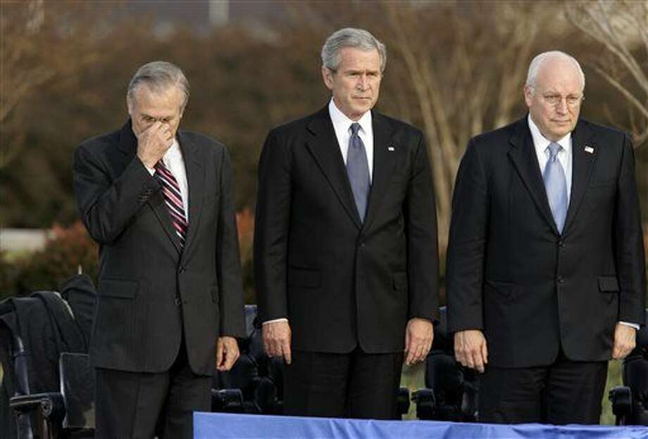 FILE - In this Friday, Dec. 15, 2006, file photo, Secretary of Defense Donald Rumsfeld, left, pauses as President George W. Bush, and Vice President Dick Cheney participate in Rumsfeld's farewell ceremony at the Pentagon in Washington. Former President George H.W. Bush is publicly criticizing for the first time key members of his son's administration. A biography of the nation's 41st president to be published in November, 2015, contains his sharply critical assessments of Cheney and Rumsfeld. (AP Photo/J. Scott Applewhite, File) Photo: J. Scott Applewhite
