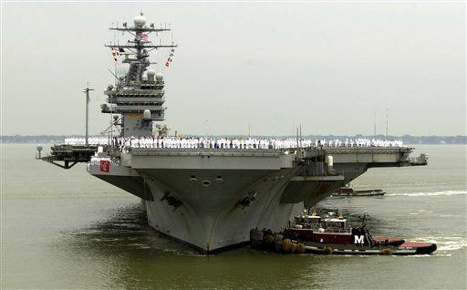 FILE - In this May 29, 2003 file photo, sailors man the rails as the USS Theodore Roosevelt is maneuvered into it's berth at the Norfolk Naval Station in Norfolk, Va. Defense Secretary Carter was flying Thursday onto the USS Theodore Roosevelt, an American aircraft carrier in the disputed waterway. Carter is using the visit to the USS Theodore Roosevelt to amplify the U.S. view that China is making excessive claims that nearly all of the South China Sea as its territory. (AP Photo/Steve Helber, File) Photo: Steve Helber