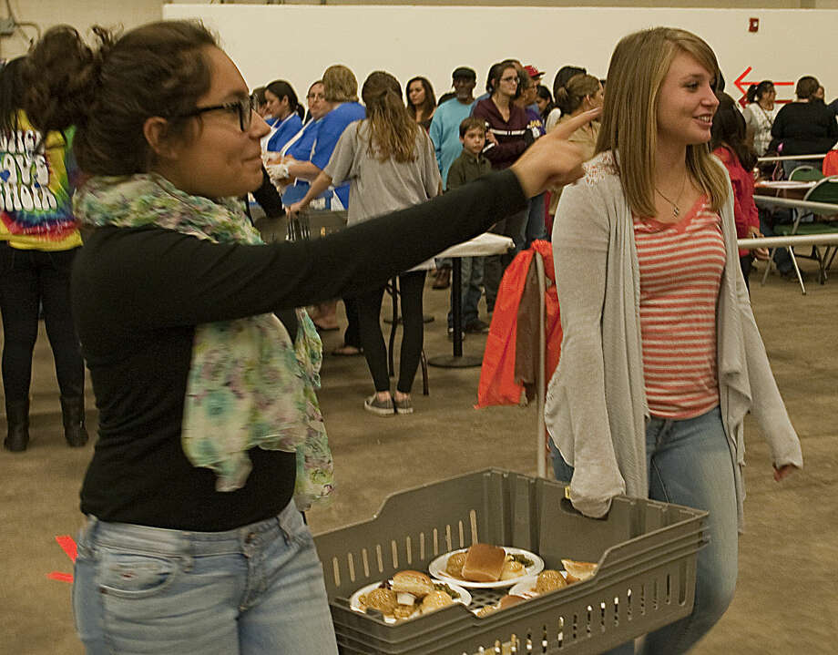 Daniela Rodriguez and Shaylee Williams as well as hundreds of other volunteers serve meals Friday at the annual Feast of Sharing. Tim Fischer\Reporter-Telegram Photo: Tim Fischer