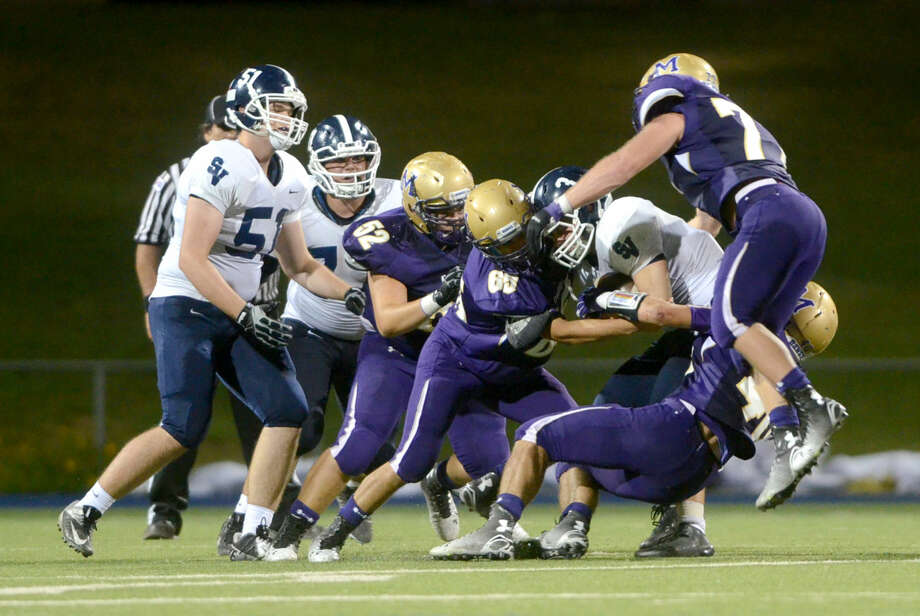 Midland High's Jacob Granado (52), Salvador Salinas (65), Jack Youngblood (40) and Coleton Whitlock (77) tackle against Smithson Valley running back Cord Given (3) on Friday at Grande Communications Stadium. Midland High beat Smithson 33-26 in double overtime. James Durbin/Reporter-Telegram Photo: James Durbin
