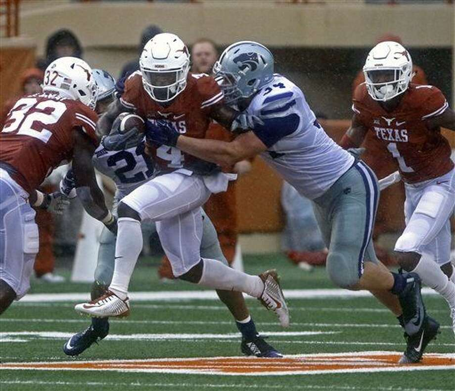 Texas running back Daje Johnson (4) runs the ball against Kansas State's Tanner Wood (34) during the first half of an NCAA college football game, Saturday, Oct. 24, 2015, in Austin, Texas. (AP Photo/Michael Thomas) Photo: Michael Thomas