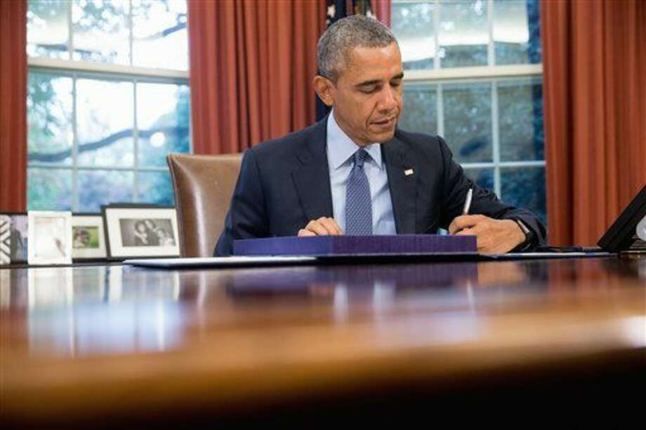 "President Barack Obama signs H.R. 1314, the ""Bipartisan Budget Act of 2015,"" Monday, Nov. 2, 2015, in the Oval Office in the White House in Washington, before traveling Andrews Air Force Base, Md., on his way to Newark, N.J. Obama will spend the day highlighting the re-entry process of formerly incarcerated individuals back into society. (AP Photo/Andrew Harnik) Photo: Andrew Harnik"