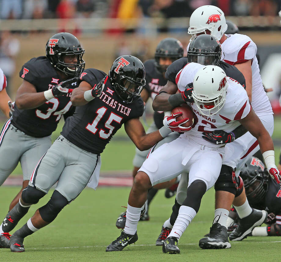 The Texas Tech defense swarms to stop Arkansass running back Jonathan Williams (32) in Saturdays matchup at Jones AT & T stadium. Photo: Wade H Clay