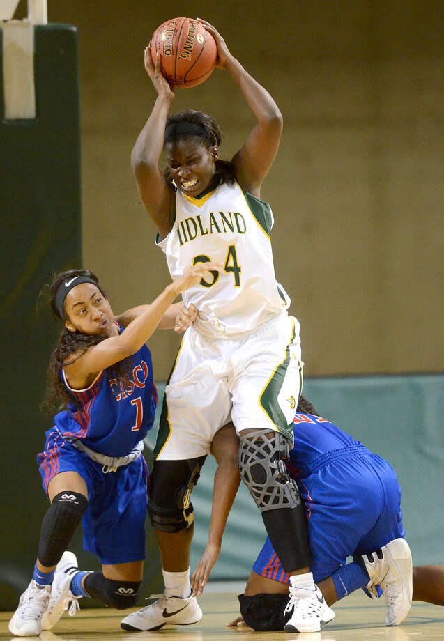 Midland College's Teneshia Dixon comes down with a rebound against Cisco's Bianca Hampton (1) and Taylor Hayes (21) on Tuesday, Nov. 11, 2015 at Chaparral Center. James Durbin/Reporter-Telegram Photo: James Durbin