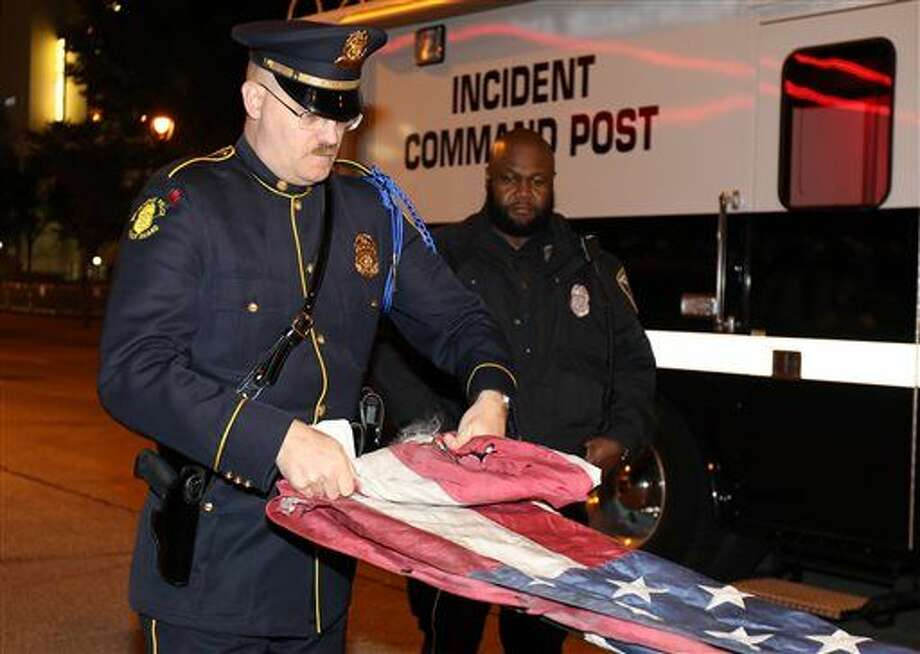 "In this photo taken on Tuesday, Nov. 10, 2015, and provided by the Milwaukee Police Department, officer Jutiki X, right, looks on as Officer Joel Rossman folds an American flag police recovered after it was set on fire by a protester outside the Republican presidential debate in Milwaukee. Milwaukee police say they've identified a protester who burned the flag. Police Chief Edward Flynn says burning a flag is protected free speech, but ""carelessly lighting a fire in the middle of a crowd"" isn't. (Jon D. Riemann/Milwaukee Police Department via AP) Photo: Jon D. Riemann"