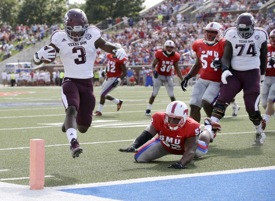 Texas A&M running back Trey Williams (3) high steps into the end zone past SMU linebacker Cameron Nwosu (52) as the Aggies' Germain Ifedi (74) watches in the first half of an NCAA college football game, Saturday, Sept. 20, 2014, in Dallas. (AP Photo/Tony Gutierrez) Photo: Tony Gutierrez