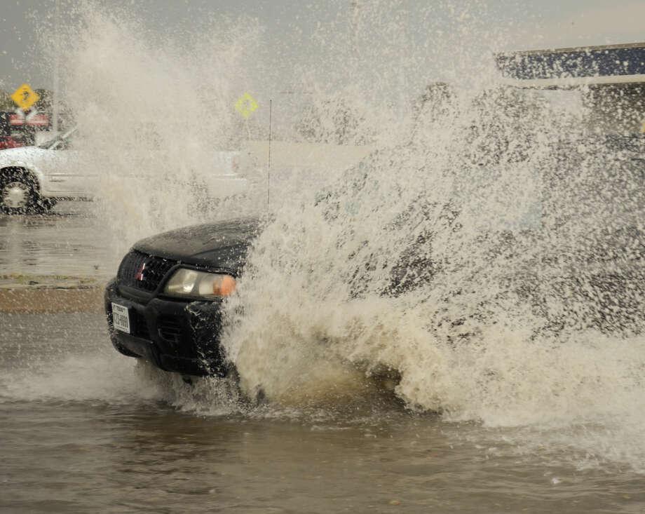 Drivers make their way along a flooded A Street Monday evening. Tim Fischer\Reporter-Telegram Photo: Tim Fischer