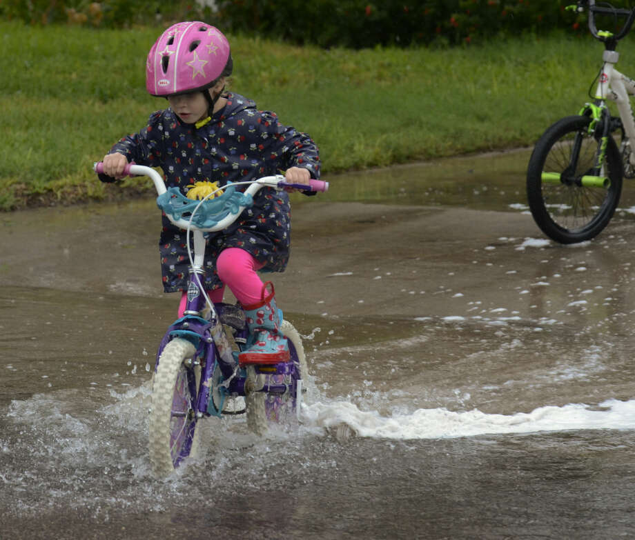 Audrey McGuire plays in the puddles outside her house on Terrace Ave. Sunday afternoon. Tim Fischer\Reporter-Telegram Photo: Tim Fischer