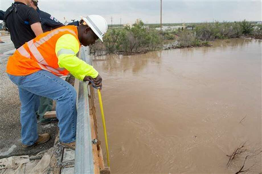 A employee from the Texas Department of Transpiration measures the depth of the Pecos River in Ward County, Texas, between Pecos and Barstow on Monday, Sept. 22, 2014. (AP Photo/The Odessa American, Courtney Sacco) Photo: Courtney Sacco