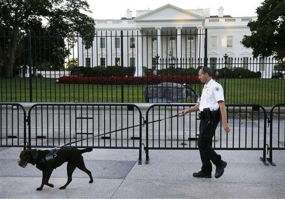 A member of the Secret Service Uniformed Division with a K-9 walks along the perimeter fence along Pennsylvania Avenue outside the White House in Washington, Monday, Sept. 22, 2014. The Secret Service tightened their guard outside the White House after Friday's embarrassing breach in the security of one of the most closely protected buildings in the world. A man is accused of scaling the White House perimeter fence, running across the lawn and entering the presidential mansion before agents stopped him. (AP Photo/Carolyn Kaster) Photo: Carolyn Kaster