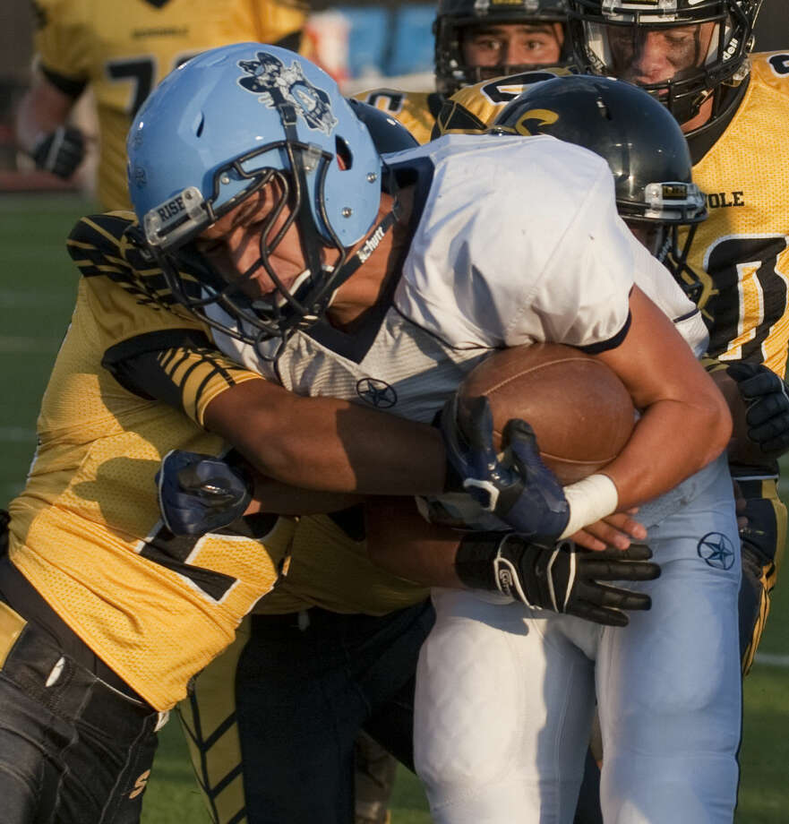 Greenwood's Javier Vizcaino gets wrapped up by Seminole's Alban Bejarano and Kason Rosales Friday evening at Wig Wam Stadium in Seminole. Tim Fischer\Reporter-Telegram Photo: Tim Fischer