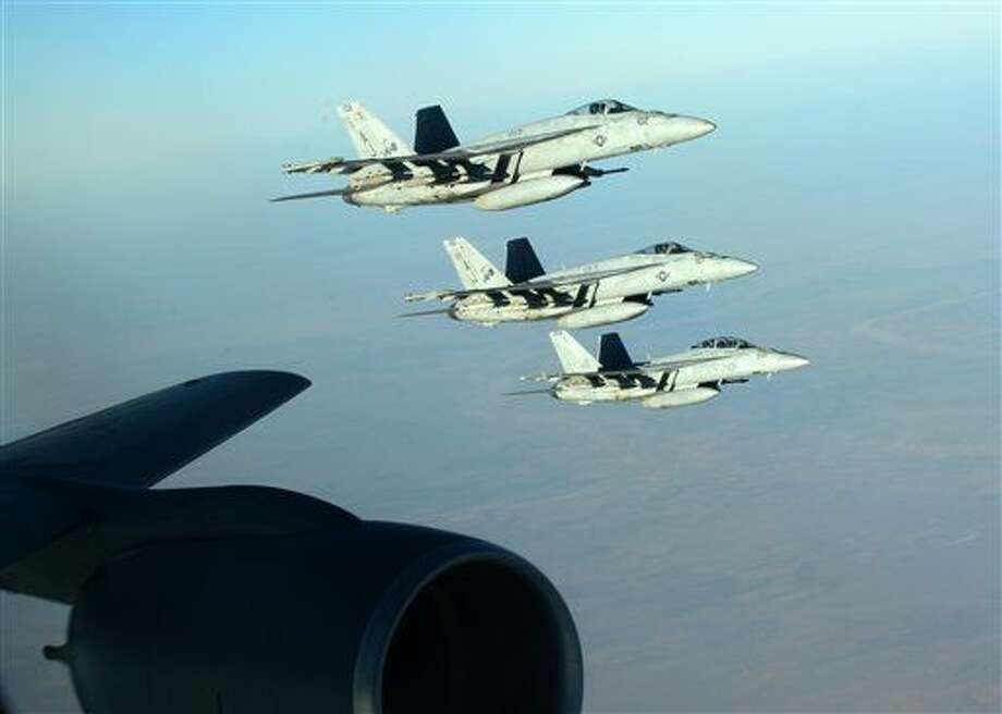 In this Tuesday, Sept. 23, 2014 photo released by the U.S. Air Force, a formation of U.S. Navy F-18E Super Hornets leaves after receiving fuel from a KC-135 Stratotanker over northern Iraq as part of U.S. led coalition airstrikes on the Islamic State group and other targets in Syria. U.S.-led airstrikes targeted Syrian oil installations held by the militant Islamic State group overnight and early Thursday, Sept. 25, 2014, killing nearly 20 people as the militants released dozens of detainees in their de facto capital, fearing further raids, activists said. (AP Photo/U.S. Air Force, Staff Sgt. Shawn Nickel) Photo: Staff Sgt. Shawn Nickel