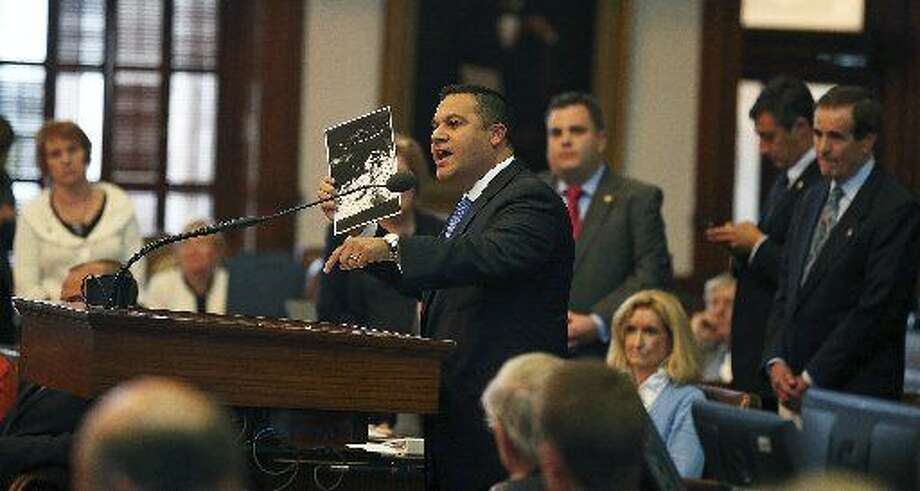 Jason Villalba (R-Dallas) shows a picture of his son still in the womb as the House of Representatives debates amendments to abortion legislation on July 9, 2013. Photo: TOM REEL