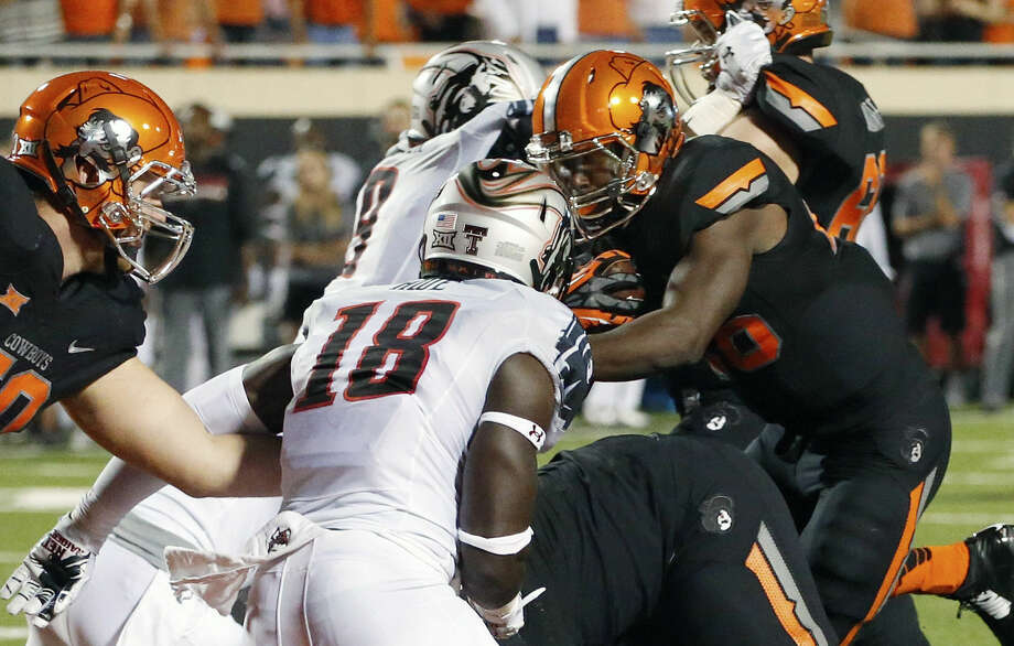 Oklahoma State running back Desmond Roland, right carries for a touchdown past Texas Tech linebacker Micah Awe (18) in the second quarter of a football game in Stillwater, Okla., Thursday, Sept. 25, 2014. (AP Photo/Sue Ogrocki) Photo: Sue Ogrocki