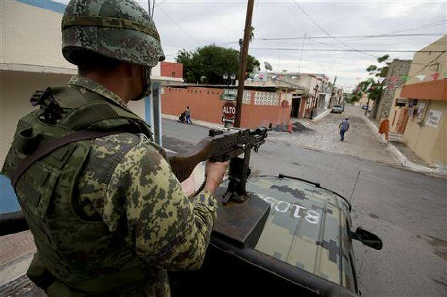 In this Sept. 5, 2014 photo, a soldier patrols from the top of a moving vehicle as residents walk in the street in Ciudad Mier, Tamaulipas state, Mexico. Mexico has sent its soldiers, marines and federal police to bring Tamaulipas state under control, as it prepares to develop rich shale fields along the Gulf Coast, and attract foreign investors. (AP Photo/Eduardo Verdugo) Photo: Eduardo Verdugo