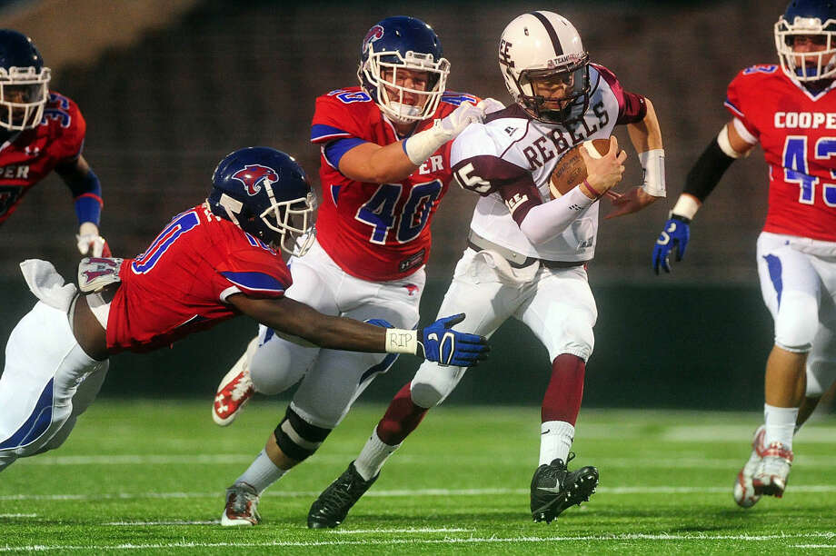 Midland Lee High's Wesley Hall is stopped by Cooper High's Josh Hale (40) and Kirey McAfee (10) during the first quarter of their game Friday, September 26, 2014 at Shotwell Stadium.