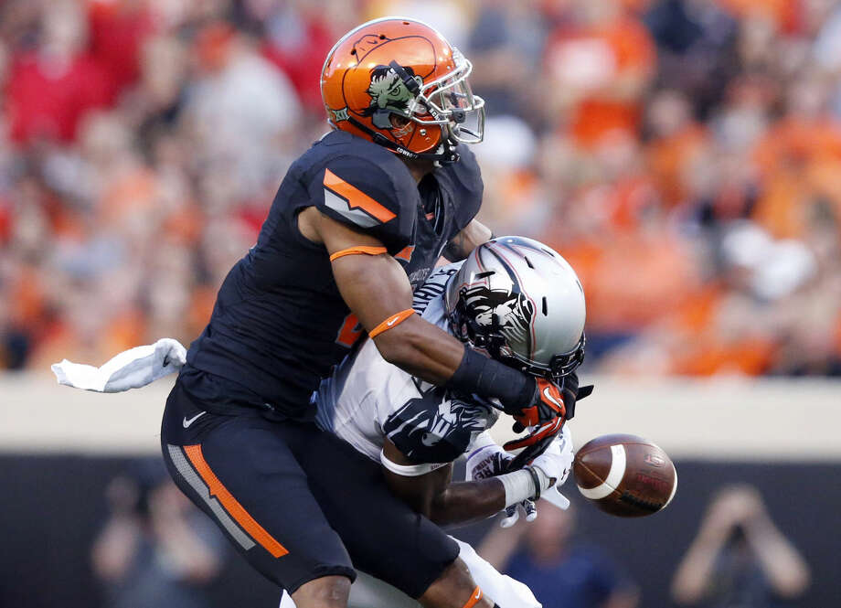 Oklahoma State cornerback Ashton Lampkin, left, breaks up a pass intended for Texas Tech wide receiver Reginald Davis, right, in the first quarter of an NCAA college football game in Stillwater, Okla., Thursday, Sept. 25, 2014. (AP Photo/Sue Ogrocki) Photo: Sue Ogrocki