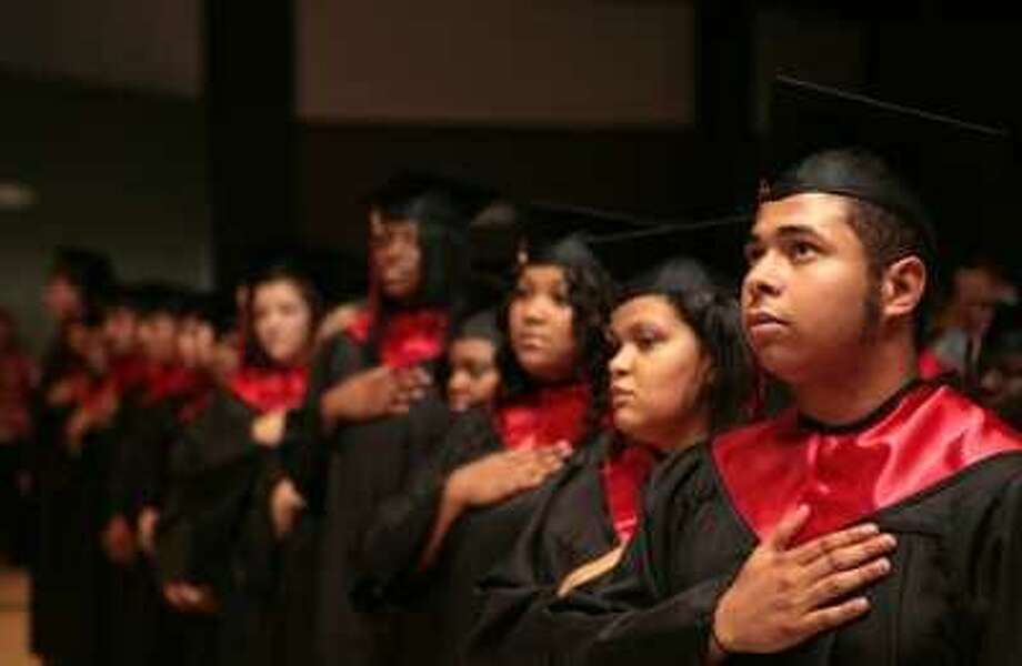 GRADUATES Viola M. Coleman High School graduate Alexander Long recites the Pledge of Allegiance with his classmates at the beginning of the ceremony in the Martin Luther King Jr. Community Center.