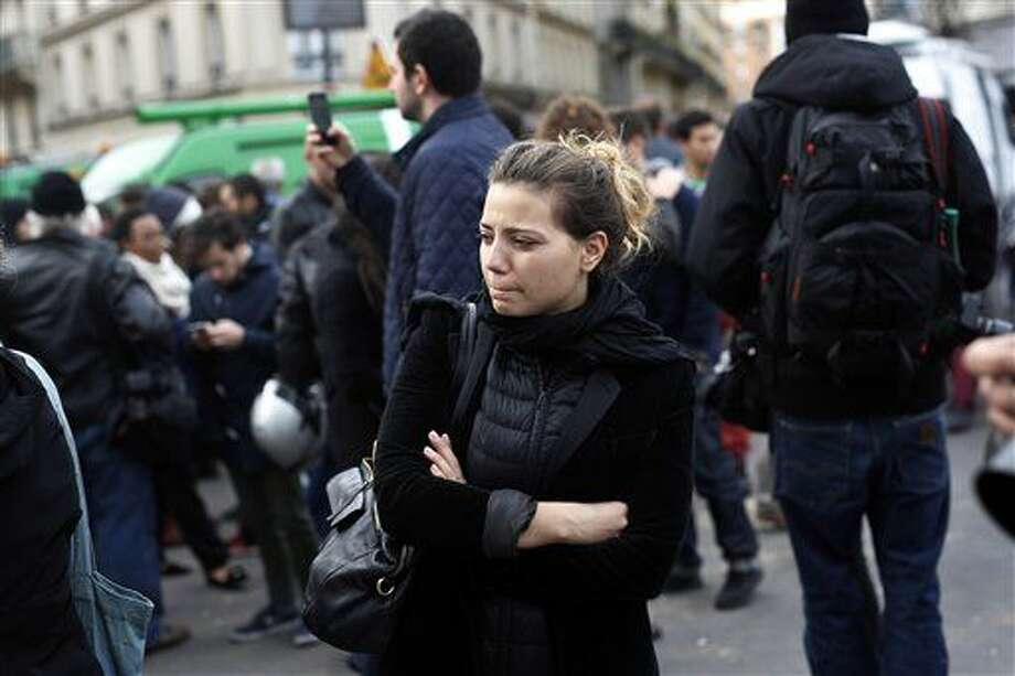 People react in front of the Carillon cafe and the Petit Cambodge restaurant in Paris Saturday Nov. 14, 2015, a day after over 120 people were killed in a series of shooting and explosions. (AP Photo/Jerome Delay) Photo: Jerome Delay