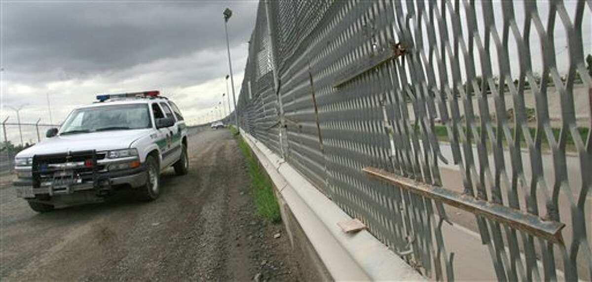 FILE - In this Aug. 3, 2007 file photo, a Border Patrol vehicle drives past a portion of the border fence, in El Paso, Texas.