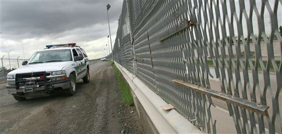 FILE - In this Aug. 3, 2007 file photo, a Border Patrol vehicle drives past a portion of the border fence, in El Paso, Texas. Photo: Victor Calzada / AP2007