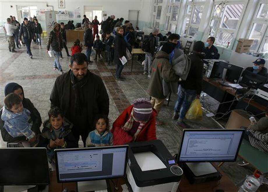 Migrants family wait to register with the police in a refugee center in the southern Serbian town of Presevo, Monday, Nov. 16, 2015. Refugees fleeing war by the tens of thousands fear the Paris attacks could prompt Europe to close its doors, especially after police said a Syrian passport found next to one attacker's body suggested its owner passed through Greece into the European Union and on through Macedonia and Serbia last month. (AP Photo/Darko Vojinovic) Photo: Darko Vojinovic