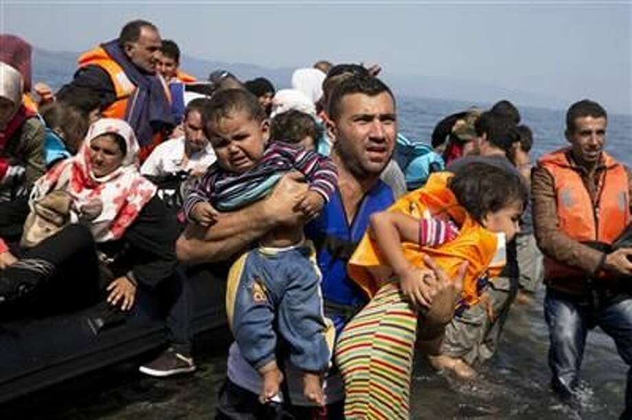 Syrian refugees arrive aboard a dinghy after crossing from Turkey to the island of Lesbos, Greece, Thursday, Sept. 10, 2015. The US is making plans to accept 10,000 Syrian refugees in the coming budget year, a significant increase from the 1,500 migrants that have been cleared to resettle in the U.S. since civil war broke out in the Middle Eastern country more than four years ago, the White House said Thursday. (AP Photo/Petros Giannakouris) Photo: Associated Press
