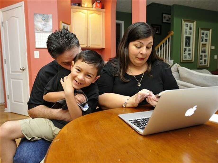 Marisela Martinez-Cola, right, a lawyer and a parent living in an Atlanta suburb with her husband Greg, left, and their 7-year-old son, David, prepare for a typical school and work day Tuesday, Sept. 30, 2014, in Lawrenceville, Ga. The couple send their son to private school and have hired a tutor to improve David's reading _ expenses made possible by Greg's salary as a regional buyer for Costco Wholesale. (AP Photo/David Tulis) Photo: David Tulis