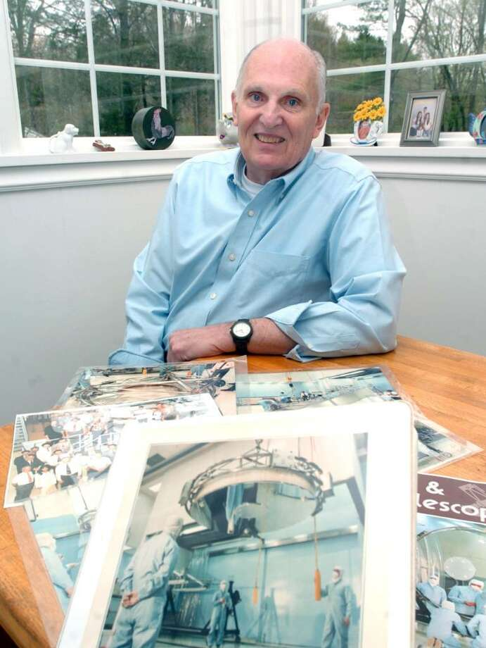 Bill Meyer, of Ridgfield, is surrounded by photographs from when he was working at Perkin-Elmer in the late 1970's to early 1980's as a manager of optical manufacturing with the Hubbel Telescope project. Photo taken Friday, April 16, 2010. Photo: Chris Ware / The News-Times