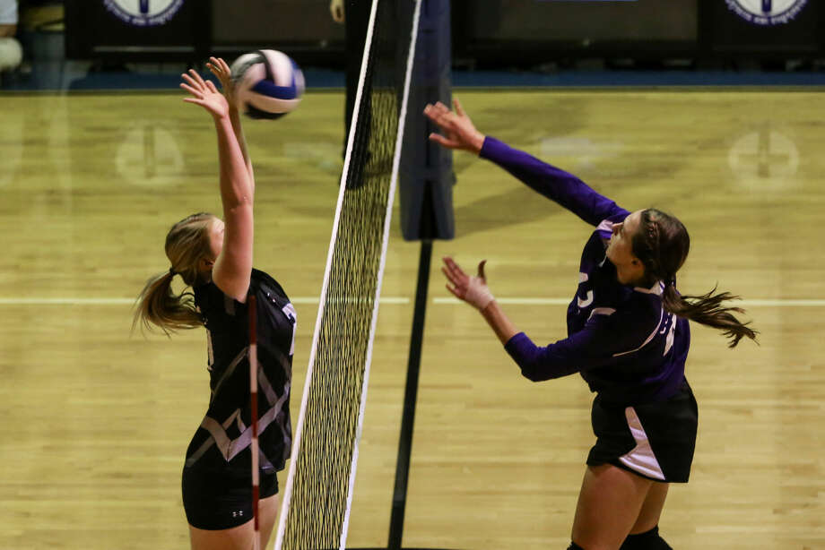 Trinity's Averee Curlee goes up for a block as Midland Classical's Kristen Johnson goes for a kill during Tuesday's match at Trinity. Claire Heck/Special to the MRT