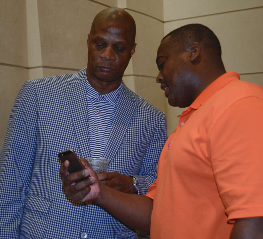 Darryl Strawberry looks at a picture with Geo Mitchell Tuesday evening at the New Direction Ministry evening with Strawberry speaking about his life in baseball and beyond. Tim Fischer\Reporter-Telegram Photo: Tim Fischer