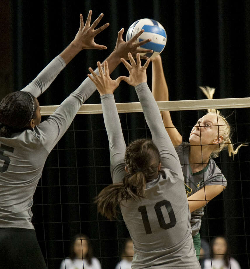 Midland College's Anne-Mari Kaur tries to put a spike down as NMMI's Mere Serea, 5, and Ariel Swaim, 10, block Wednesday at the Chaparral Center. Tim Fischer\Reporter-Telegram Photo: Tim Fischer