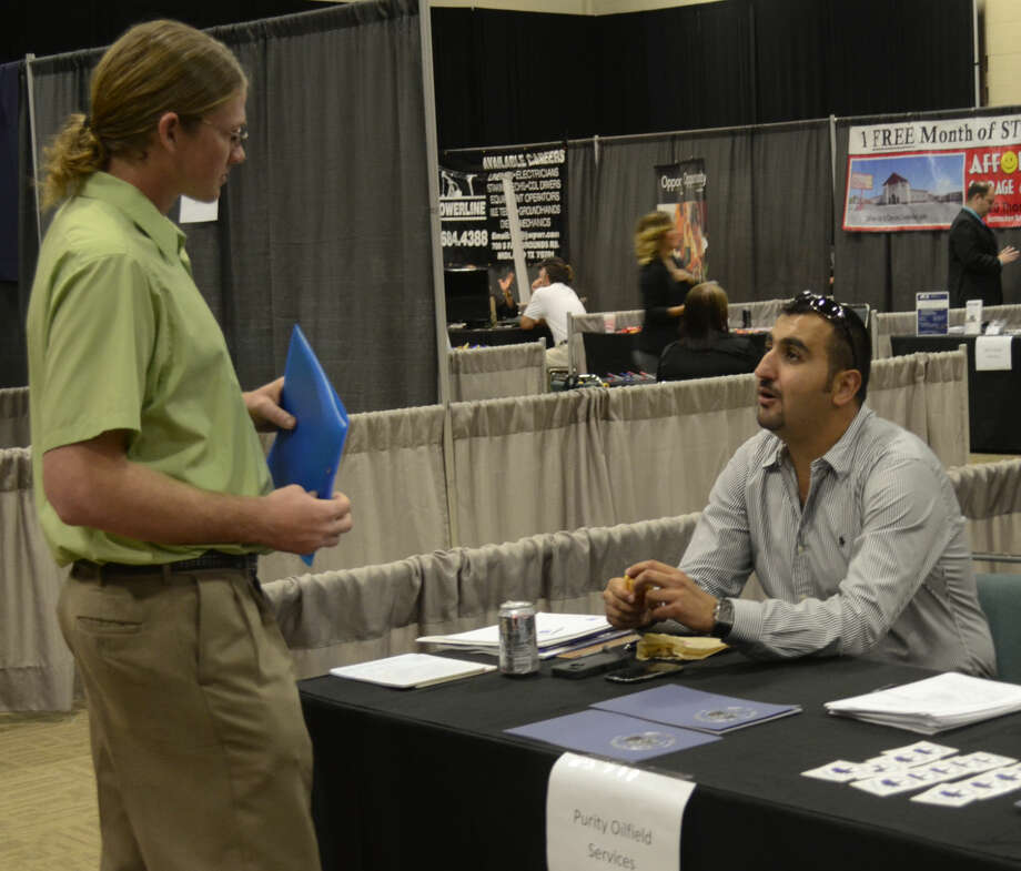 Chris Yonan dispatch manager with Purity Oilfield Services, right, talks with Joseph Ely Tuesday at the MRT Career Fair at the Midland Center. Tim Fischer\Reporter-Telegram Photo: Tim Fischer