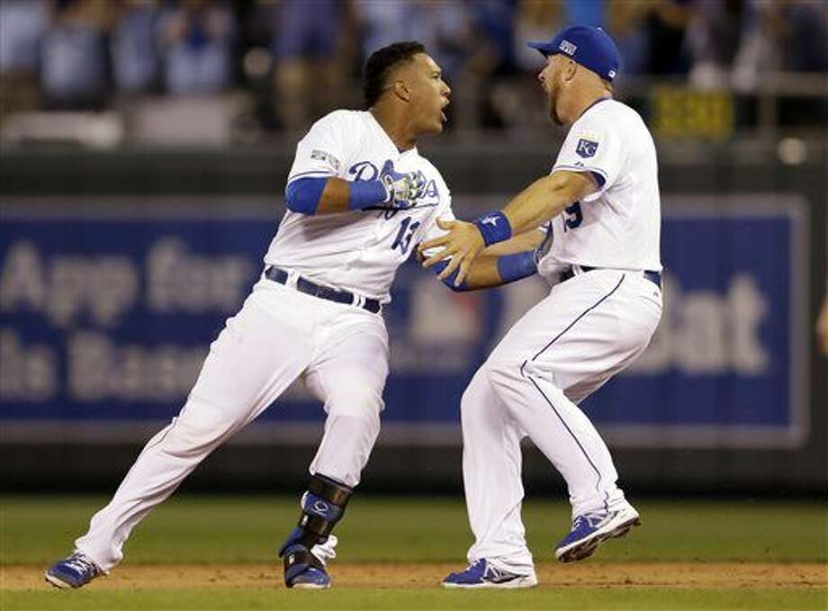 Kansas City Royals' Salvador Perez, left, is congratulated by Erik Kratz after hitting a walk-off single in the 12th inning to defeat the Oakland Athletics 9-8 in the AL wild-card playoff baseball game Tuesday, Sept. 30, 2014, in Kansas City, Mo. (AP Photo/Jeff Roberson) Photo: Jeff Roberson