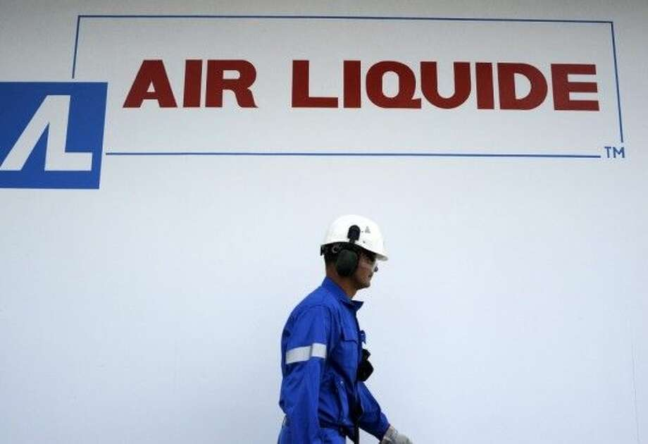 A worker passes by an Air Liquide logo at the Air Liquide hydrogen plant in Port Jerome, France, on Friday, July 24, 2009. The company announces its earnings next week. Photo: Photographer: Fabrice Dimier/Bloomberg