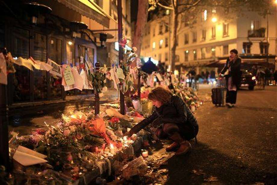 A woman lights a candle near the Cosa Nostra restaurant, in Paris, Friday Nov.20, 2015. French President Francois Hollande will preside over a national ceremony Nov. 27 honoring the victims of the deadliest attacks on France in decades.(AP Photo/Thibault Camus) Photo: Thibault Camus